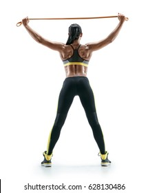 Strong woman performs exercises for the muscles of the back and hands with resistance band. Rear view of fitness model with athletic body isolated on white background. Strength and motivation.
