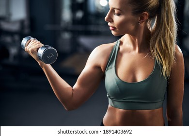 Strong woman pumping iron in a gym with the help of three-kilo dumbbell in her hand