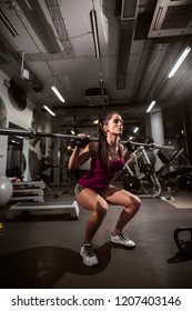 Strong woman in sportswear doing quats while holding weight bar on her shoulders.