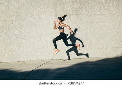Strong woman in sportswear running and exercising outdoors. Caucasian female doing running workout in morning.