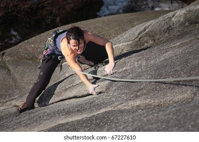 A strong woman struggles up a steep rock face in Squamish British Columbia Canada.