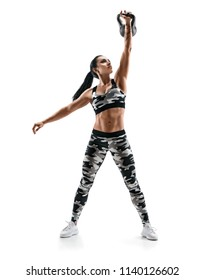 Strong woman training with kettlebell. Photo of latin woman in military sportswear isolated on white background. Strength and motivation. Full length