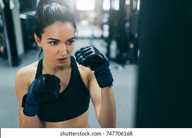 Strong woman training and punching a bag with kickboxing gloves in the gym workout. Sport, fitness, lifestyle and people concept.