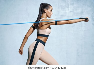 Strong woman using resistance band in her exercise routine. Photo of fitness model workout on grey background. Strength and motivation