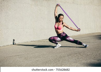Strong woman using a resistance band in her exercise routine. Fitness female doing stretching workout outdoors.