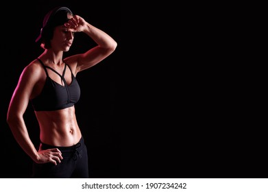 Strong woman wearing sports bra with muscular abdomen listen music in headphones over black background. Perfect Body Shape