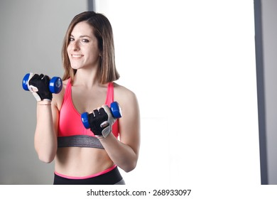 Strong woman weightlifting at the gym looking happy.