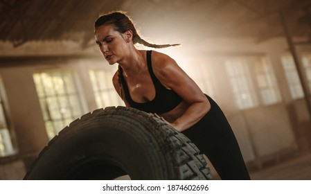 Strong woman working out with a huge tire in cross workout space. Woman exercising with big tire at an abandoned warehouse.