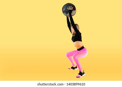 Strong woman workout with med ball. Photo of sporty latin woman in fashionable sportswear on yellow background. Strength and motivation.