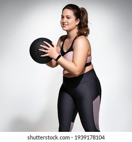 Strong woman workout with medicine ball. Photo of model with curvy figure in fashionable sportswear on grey background. Sports motivation and healthy lifestyle