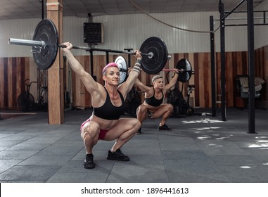 Strong women bodybuilder doing overhead with heavy barbell in modern gym. Functional training class. Bodybuilding and Fitness