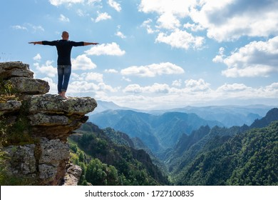 A strong young bald man stands on the edge of a precipice with his arms outstretched and balancing. Meditation and freedom, yoga in harmony with nature.