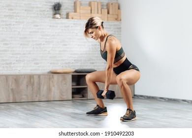 Strong young blonde woman doing heavy dumbbell exercise in gym. Female doing squats.