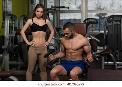 Strong Young Couple Working Out With Dumbbells For Biceps In The Gym With Exercise Equipment