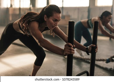 Strong young female pushing the prowler exercise equipment. Fit women exercising at gym.