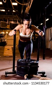 Strong young female pushing sleds in gym