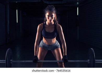 Strong young fitness girl with weights on her hands exercise in gym