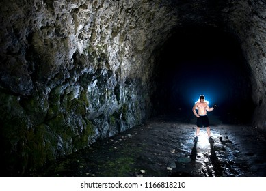 Strong young male lifting dumbbells in a cave