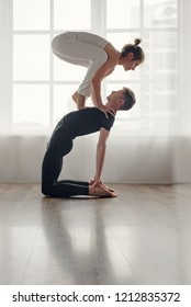Strong young man balancing woman while doing yoga asana