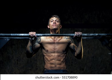 Strong young man doing pull up exercise on horizontal bar in gym. Sports, fitness, gymnastics workout.
