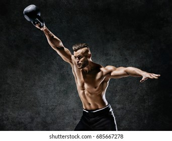 Strong young man swinging a kettlebell on dark background. Strength and motivation.