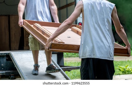 strong young men moving furniture into a moving van