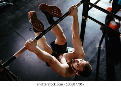 Strong young muscular man doing toes to bar exercise at the gym.