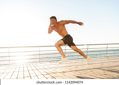 Strong young shirtless sportsman in earphones running at the seaside
