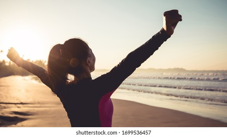 Starke junge Frau mit offenen Armen am Sonnenaufgangsstrand