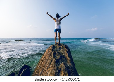 Strong young woman outstretched arms on seaside rock cliff edge