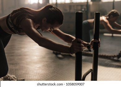 Strong young woman pushing the sled at gym. Women doing intense physical workout in gym.