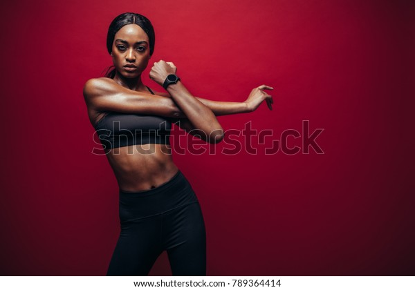 Strong young woman stretching her arms. Portrait of african woman working out against red background.