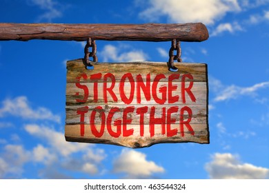 Stronger together motivational phrase sign on old wood with blurred background