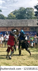 STRONSKO, POLAND - August 4, 2018: knights in full armor are fighting during a reenactment of a battle of medieval knights during a historical festival in Stronsko, Poland.