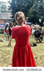 STRONSKO, POLAND - August 4, 2018: a blond woman in a red dress in taking a photo during a reenactment of a battle of medieval knights at a historical festival in Stronsko, Poland.