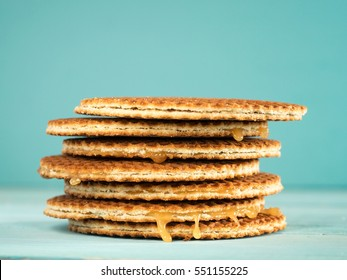 Stroopwafels or caramel Dutch Waffle close up on turquoise wooden background