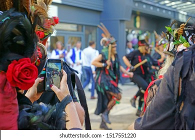 Stroud, Gloucestershire, UK, September 21st, 2019, Styx of Stroud Border Morris dancing to the music in their traditional costumes while a member of the group films them on her mobile phone.