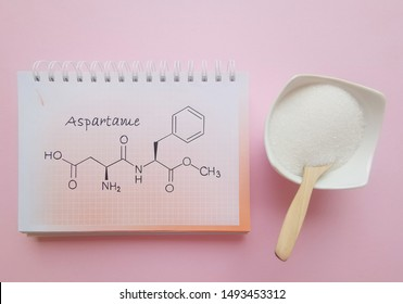 Structural chemical formula of aspartame molecule with artificial sweetener in white bowl. Aspartame is an artificial sweetener used as a sugar substitute in some foods and beverages.