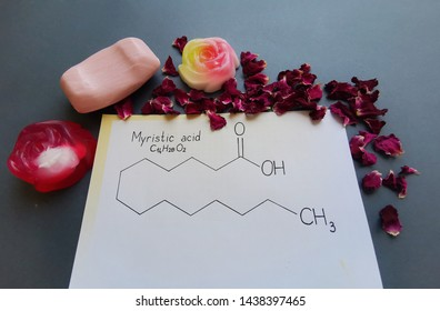 Structural chemical formula of myristic (tetradecanoic) acid molecule with homemade soaps and rose petals. Myristic acid is a saturated long-chain fatty acid, used in soap making. Skeletal formula.