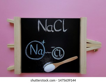 Structural chemical formula of sodium chloride molecule on a black chalkboard with spoonful of table salt. Sodium chloride (NaCl, salt, halite) is a crystal, odorless substance, with a salty taste.