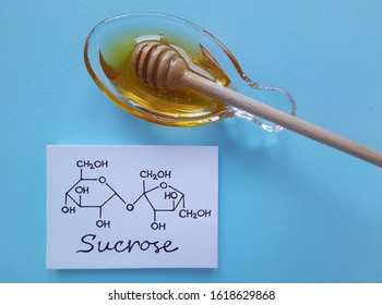 Structural chemical formula of sucrose molecule with a bowl of honey. It is a disaccharide molecule composed of glucose and fructose. Honey gets its sweetness from fructose, glucose, and sucrose.