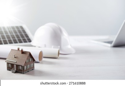 Structural engineer and architect desktop with safety helmet, solar panel and model house