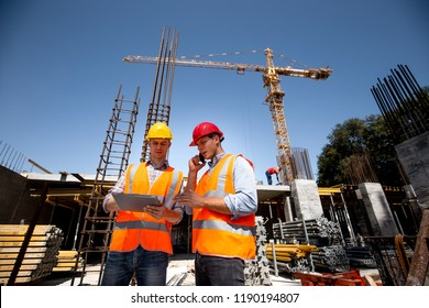 Structural engineer and architect dressed in orange work vests and  hard bats  discuss the construction process by the phone and use tablet  on the open building site near the crane