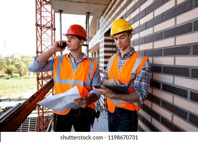 Structural engineer and architect dressed in orange work vests and  helmets discuss the construction process, use a phone and tablet on the balcony of building under construction
