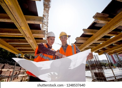 Structural engineer and architect dressed in shirts, orange work vests and helmets explore construction documentation on the building site near the wooden building constructions