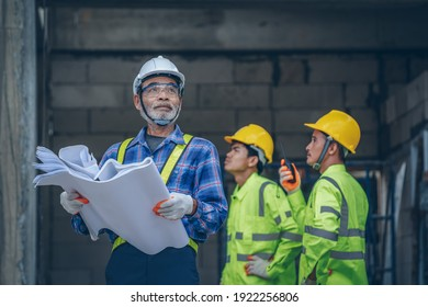 Structural engineer and architect wearing protective helmet with blueprint works on the building site.