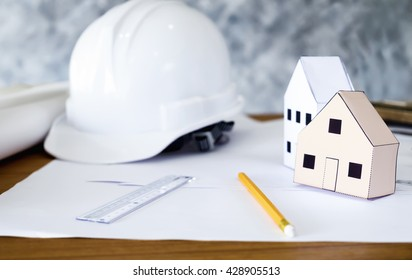 Structural engineer and architect working desktop with safety helmet and paper model houses. Construction engineering concept.