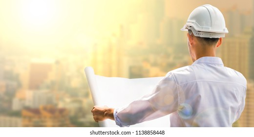 Structural engineers are going to be drafted on white paper,on the big city background at sunrise.