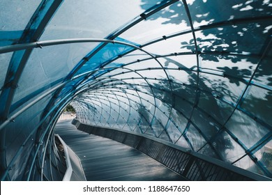 Structural glass facade curving roof and the wooden pathway inside. Modern and Contemporary architectural fiction with glass steel column.Abstract architecture fragment.  Anyang art park in korea