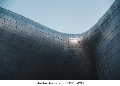 Structural glass facade curving roof and the wooden pathway inside. Modern and Contemporary architectural fiction with glass steel column.Abstract architecture fragment. Dongdaemun Design Plaza (DDP)